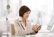 wykonawczej kobiety dojrzały biurowy smartphone używać obraz stock