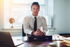 Wykonawczy biznesowy mężczyzna przy jego biurkiem fotografia stock