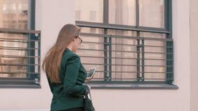 Wykonawczy bizneswoman wyszukuje smartphone podczas gdy chodzący wzdłuż budynku biurowego zbiory wideo
