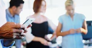 Wykonawczy używa telefon komórkowy przy biurem zbiory