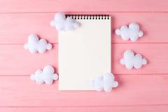 Wykonuje ręcznie białe chmury z notatnikiem, copyspace na różowym drewnianym tle Ręcznie robiony filc zabawki niebo abstrakcyjne Fotografia Stock