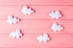 Wykonuje ręcznie białe chmury z ramą, copyspace na różowym drewnianym tle Ręcznie robiony filc zabawki niebo abstrakcyjne Zdjęcie Stock