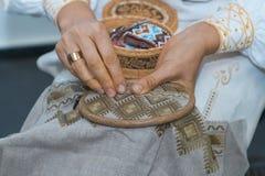 Wykonuje ręcznie broderię, kobiet ręki dekoruje handmade bieliźnianą kanwę z kolor nicią, haftuje tradycyjnego Ukraininan ornamen zdjęcia stock