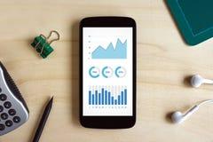 Wykresów i map elementy na smartphone ekranie na drewnianym biurku Zdjęcia Stock