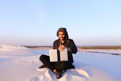 Wykształcony Arabski uczeń używa laptop i pracuje obsiadanie na piasku wśród Fotografia Royalty Free