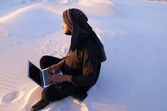 Wykształcony Arabski uczeń używa laptop i pracuje obsiadanie na piasku wśród Obraz Stock