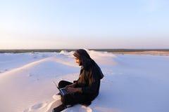 Wykształcony Arabski uczeń używa laptop i pracuje obsiadanie na piasku wśród Zdjęcie Royalty Free