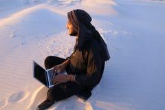 Wykształcony Arabski uczeń używa laptop i pracuje obsiadanie na piasku wśród Zdjęcia Stock