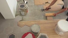 Wykwalifikowani robotnicy kłaść parkietowe podłogowe deski Mężczyzny ciupnięcia deska z młotem zbiory wideo