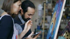 Wykwalifikowany artysty nauczyciel pokazuje podstawy obraz i dyskutuje uczeń przy klasą zdjęcie wideo
