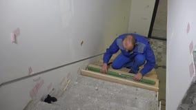 Wykwalifikowany robotnik góry drewniana deska na schody i czeka schodkach równych zbiory wideo