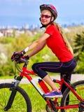 Wylotowy miastowy Rowerowa dziewczyna jest ubranym hełma odpoczynek od miasto urbanizaci Obrazy Stock