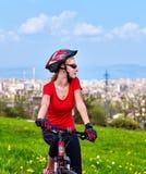 Wylotowy miastowy Rowerowa dziewczyna jest ubranym hełma odpoczynek od miasto urbanizaci Zdjęcia Stock