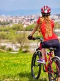 Wylotowy miastowy Rowerowa dziewczyna jest ubranym hełma odpoczynek od miasto urbanizaci Fotografia Royalty Free