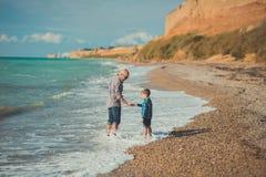 Wymarzona dotyk scena przystojny ojca odprowadzenie na dennej strony kamienia plaży z ślicznym synem jest ubranym eleganckich ubr Zdjęcie Royalty Free