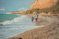 Wymarzona dotyk scena przystojny ojca odprowadzenie na dennej strony kamienia plaży z ślicznym synem jest ubranym eleganckich ubr Zdjęcia Royalty Free