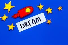 Wymarzony pojęcie Ręki literowania sen przy błękitnym kosmosu tłem z rakiety i gwiazd odgórnego widoku kopii przestrzenią obraz stock
