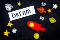 Wymarzony pojęcie Ręki literowania sen przy czarnym kosmosu tłem z rakiety i gwiazd odgórnym widokiem obraz stock