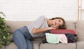 wymarzony wakacje Kobieta z walizki obsiadaniem na kanapie obrazy stock
