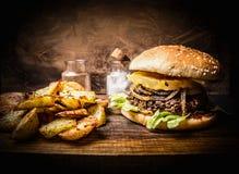 Wyśmienicie domowej roboty hamburger z mięsem, cebulami, sałatą i ananasem, kartoflani kliny na drewnianym nieociosanym tnącej de Zdjęcia Stock