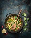 Wyśmienicie odparowani zdrowi warzywa w kulinarnej niecce z składnikami i drewnianą łyżką na ciemnym nieociosanym tle, odgórny wi Zdjęcie Stock