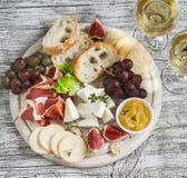 Wyśmienicie zakąska wino - baleron, ser, winogrona, krakers, figi, dokrętki, dżem, słuzyć na lekkiej drewnianej desce i dwa szkła Obrazy Stock