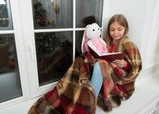 wyobraźnie Małe dziecko czyta książkę królik zabawka na wigilii Mała dziewczynka cieszy się czytelniczą Bożenarodzeniową opowieść fotografia royalty free