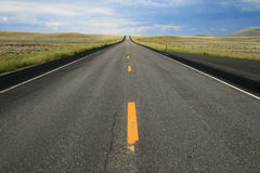 Wyoming road. A car crests the distant hill on an empty road in Wyoming royalty free stock image