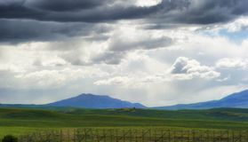 Wyoming Vast Landscape under dark clouds. Views of Wyoming`s ominous cloudy skies over open fields and sections of the Laramie Mountain Range, seen from highway stock photos