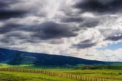 Wyoming Vast Landscape under dark clouds. Views of Wyoming`s ominous cloudy skies over open fields and sections of the Laramie Mountain Range, seen from highway stock images
