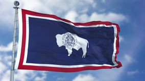 Wyoming Waving Flag. Wyoming U.S. state flag waving against clear blue sky, close up, isolated with clipping path mask luma channel, perfect for film, news royalty free stock images