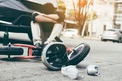 Wypadek który zdarzał się mężczyzny który pił alkohol i pijącego stres z trzaska dziecka rowerem na ziemi zdjęcie royalty free