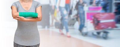 Wypadek na ręce, Zdradzonej kobiecie z zieleni obsadą na ręce i ręce na podróżniku w ruch plamie w lotnisku, Zdjęcie Stock