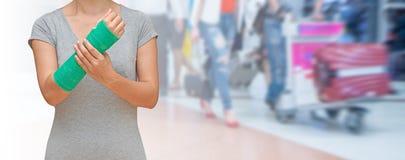 Wypadek na ręce, Zdradzonej kobiecie z zieleni obsadą na ręce i ręce na podróżniku w ruch plamie w lotnisku, Zdjęcia Stock