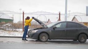 Wypadek samochodowy Młoda kobieta stoi bezczynnie łamanego samochód i otwiera samochodowego kapiszon zdjęcia stock