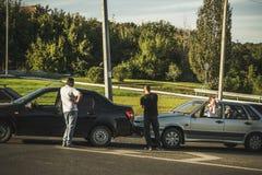 Wypadek samochodowy na drodze, dwa łamanych samochodach i kierowcach po kraksy samochodowej, zdjęcia royalty free