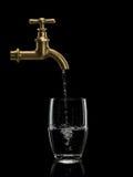 Wypełniać wodą szkło od mosiężnego faucet Obrazy Royalty Free