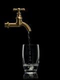Wypełniać wodą szkło od mosiężnego faucet Zdjęcie Royalty Free