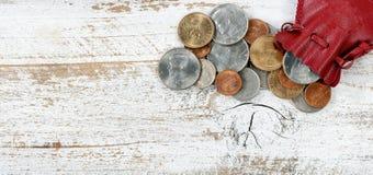 Wypełniająca rzemienna torba Stany Zjednoczone monety na białym nieociosanym drewnie zdjęcie stock