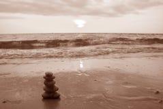 Wypiętrzający up otoczaków kamienie na zmierzchu wyrzucać na brzeg w sepiowym brzmieniu Zdjęcia Royalty Free