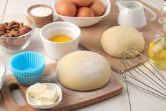 wypiekowi składniki wypiekowi narzędzia ciasto i masło, jajka, cukier, mleko, cynamon, migdały na białym drewnianym tle zdjęcia stock