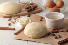 wypiekowi składniki wypiekowi narzędzia ciasto i masło, jajka, cukier, mleko, cynamon, migdały na białym drewnianym tle fotografia royalty free