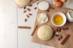 wypiekowi składniki wypiekowi narzędzia ciasto z masłem, jajka, cukier, mleko, cynamon, migdały na białym drewnianym tle Widok od zdjęcie royalty free