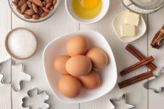 wypiekowi składniki wypiekowi narzędzia masło, jajka, cukier, mleko, cynamon, migdały na białym drewnianym tle na widok zdjęcia royalty free