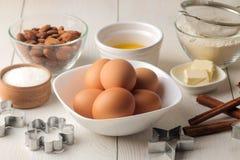 wypiekowi składniki wypiekowi narzędzia masło, jajka, cukier, mleko, cynamon, migdały na białym drewnianym tle na widok zdjęcia stock