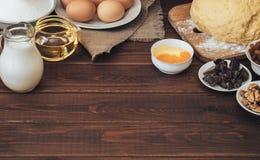 Wypiekowi składniki dla domowej roboty ciasta na ciemnym nieociosanym drewnianym tle Zdjęcia Stock