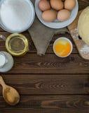 Wypiekowi składniki dla domowej roboty ciasta na ciemnym nieociosanym drewnianym tle pionowo Zdjęcie Royalty Free