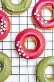 Wypiekowy minimalny pojęcie - odgórny widok świezi piec donuts z jaskrawym menchii i zieleni lodowaceniem, gwiazda kropi na de zdjęcia stock