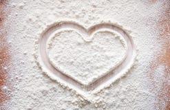 Wypiekowy pojęcie na drewnianym tle, rozpryskana mąka z sercem, kopii przestrzeń obrazy stock