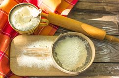 Wypiekowy tło Kulinarni składniki dla ciasta i ciasta robi i kropiących z mąki deską na nieociosanym drewnie Odgórny widok z co Zdjęcia Royalty Free